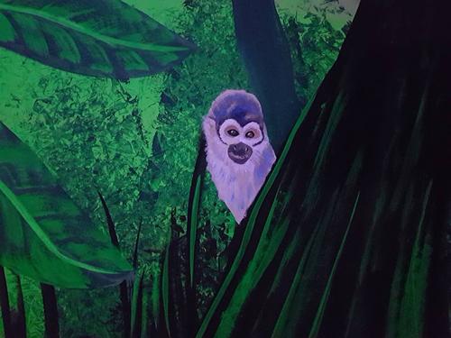 Wandmalerei, Affe im Urwald, bei Schwarzlicht.